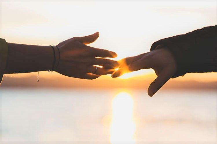 Perdonar y hacer las paces. Manos tocándose